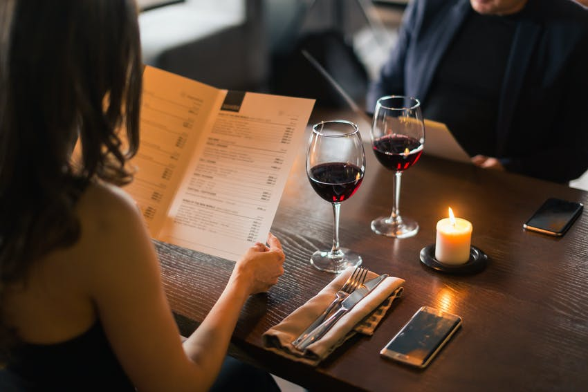 couple dining out and drinking red wine look at menu's before ordering food