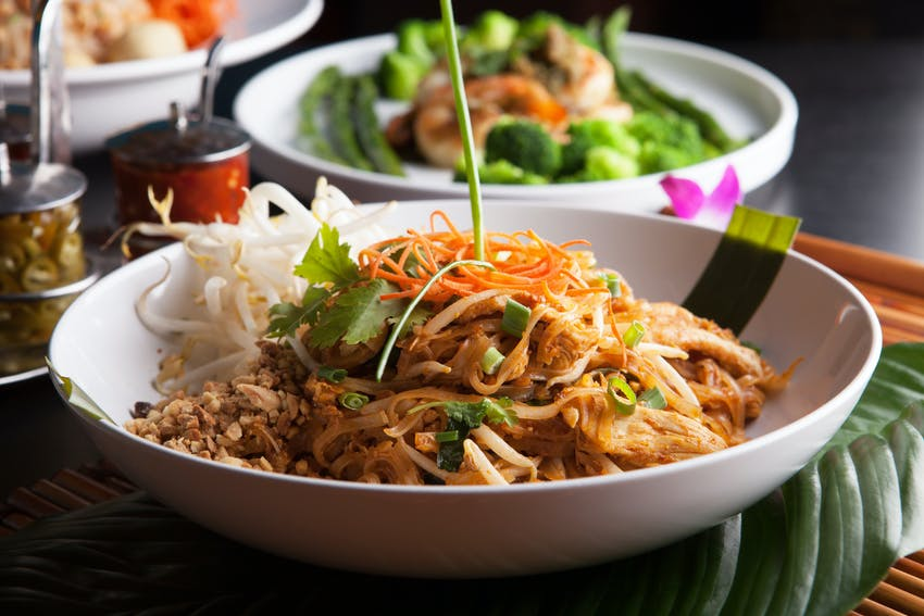 pad thai consisting of rice noodles, chicken, peanuts, eggs, bean sprouts and vegetables in a white dish