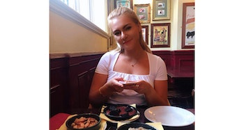 a young girl smiling at a restaurant dinner table behind three plates of tapas