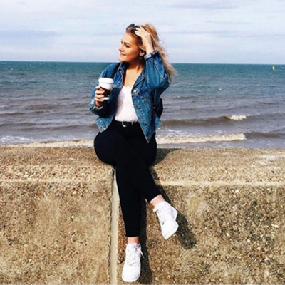 a young girl in black jeans a white top white trainers and a denim jacket on the beach wallfront holding a dairy free coffee