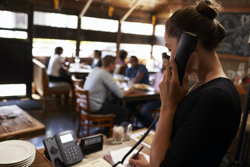 woman takes restaurant orders over the phone and writes them down on the front desk