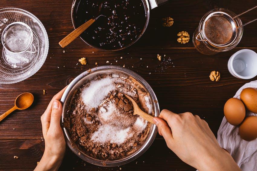 woman mixes gluten free flour into bowl to create cake mixture