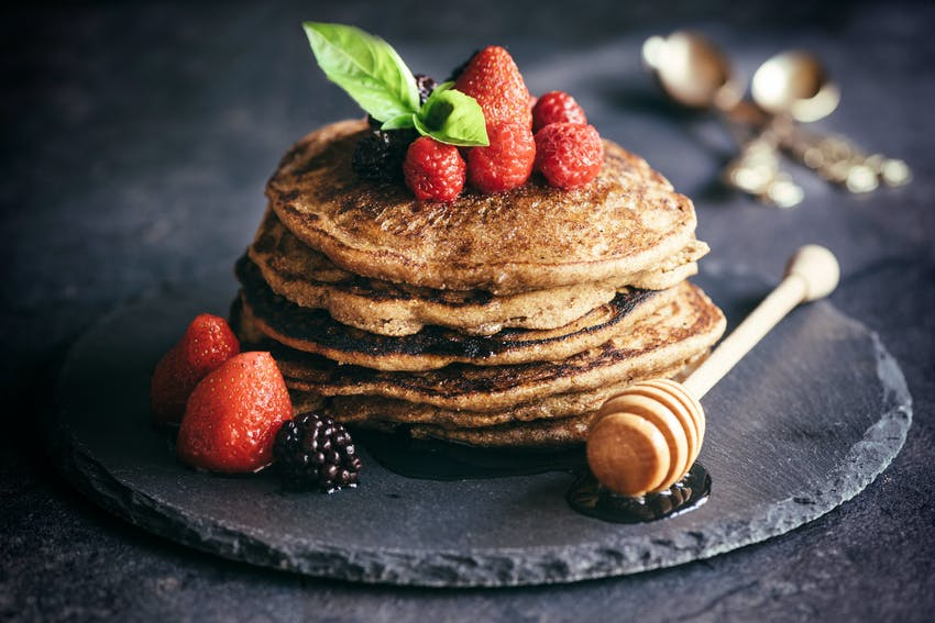 stack of fluffy gluten free pancakes with berries and honey