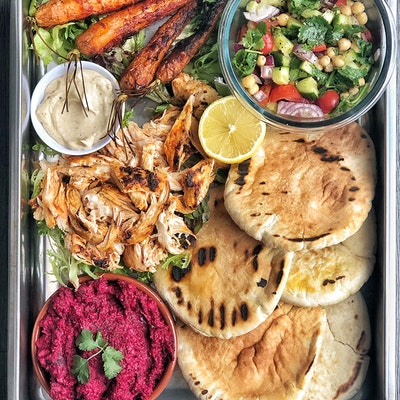 baking tray of harissa chicken pittas with baked carrots vegetables shredded chicken and beetroot dip