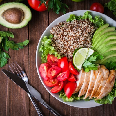 a healthy dish made up of avocado, salmon, whole grains, tomato and salad