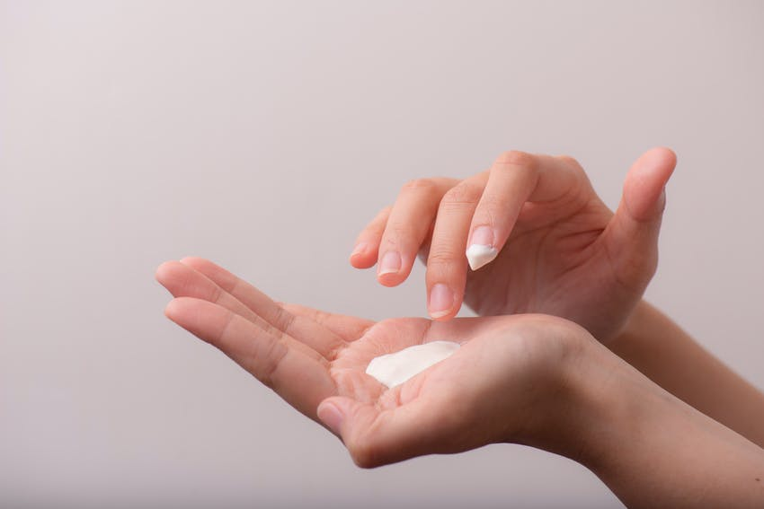 woman applying cream to hand to help soothe itchy skin from an allergic reaction