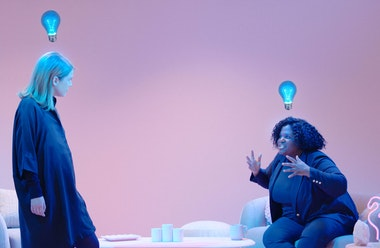 Two women talking with spooky blue lightbulbs floating above their heads.