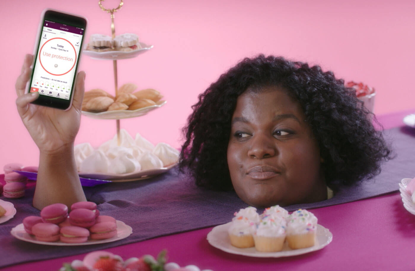Woman with her head sticking through a table laden with cake holding a phone which has a screen showing the text 'not fertile'.