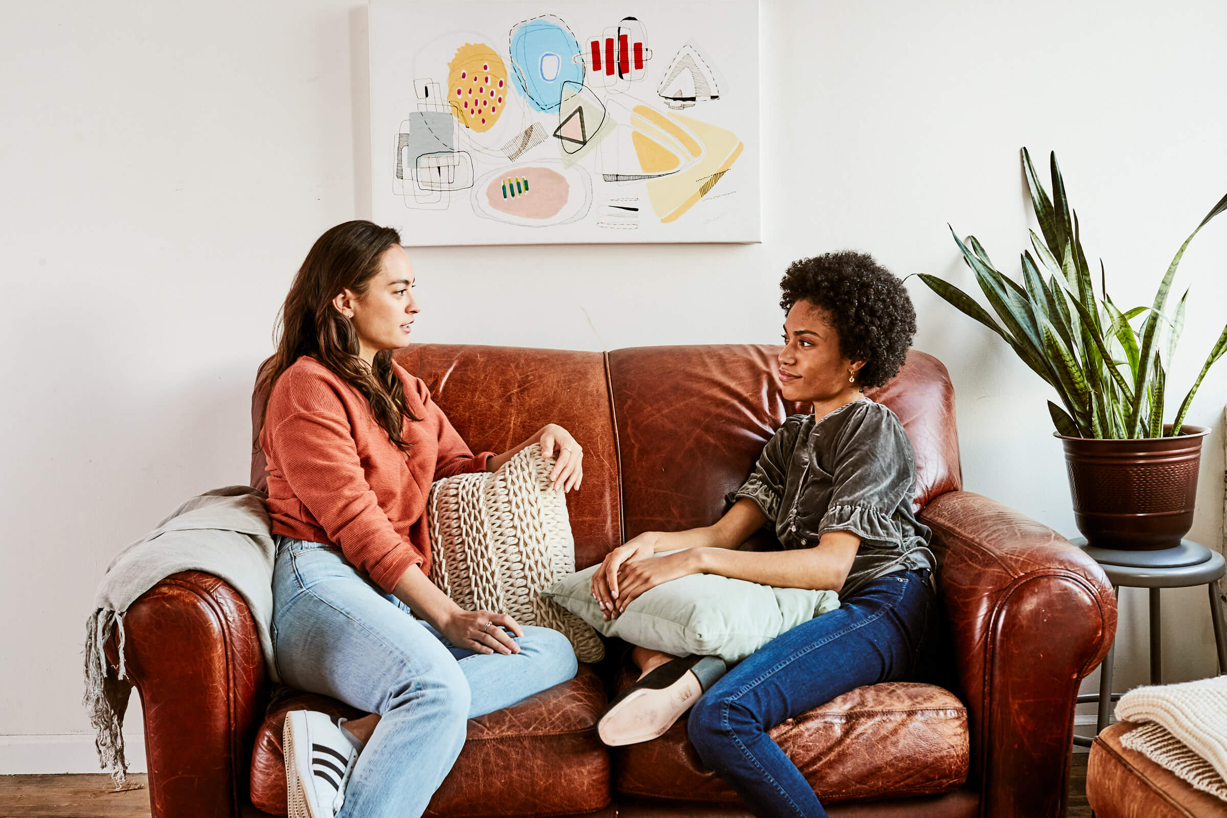 Two women sitting on a leather sofa and chatting.