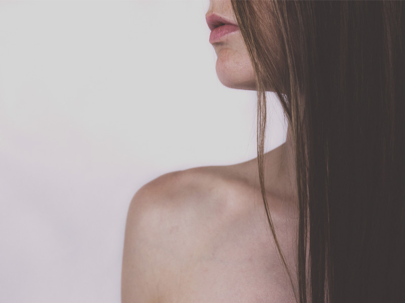 Profile of a woman with bare shoulder and long hair covering her face