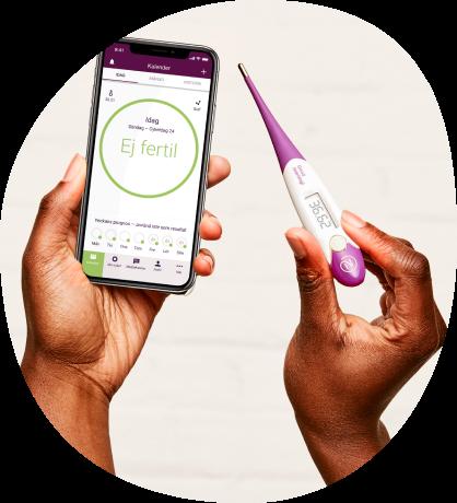 Ett par händer där den högra håller i en telefon med Natural Cycles app och den vänstra håller i Natural Cycles termometer