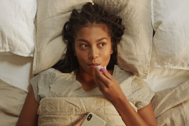 woman lying in bed measuring her temperature with a thermometer