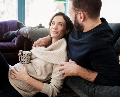 couple lying in their sofa while the woman is drinking tea and holding her pregnant belly