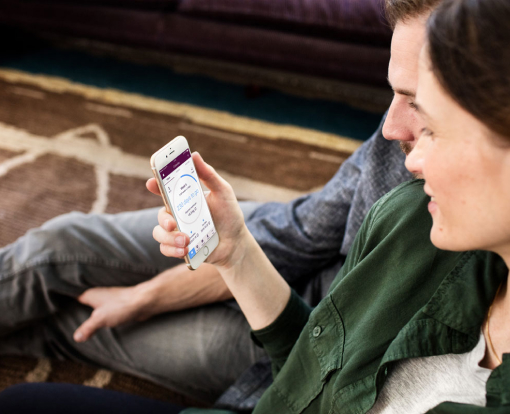 casal sentado perto um do outro olhando para o status do modo acompanhar gravidez no aplicativo do Natural Cycles