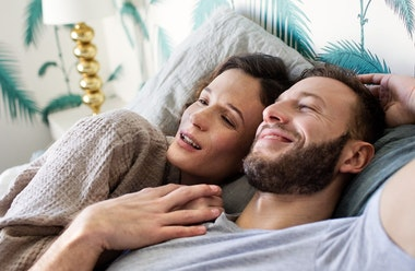 Couple holding hands and laughing in bed