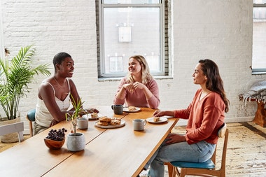 3 Women sitting round a table having coffee and talking
