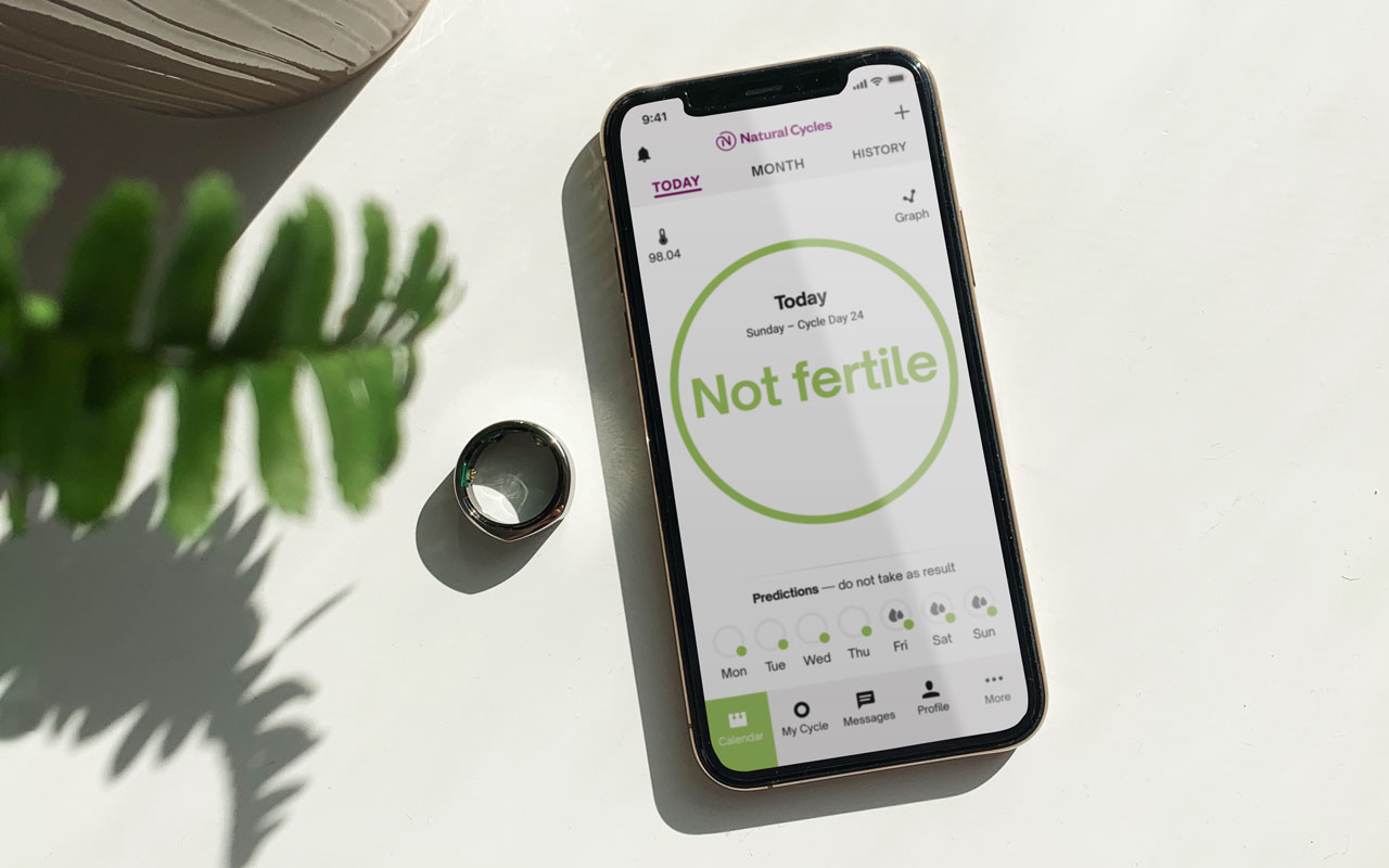 An iPhone displaying the Natural Cycles app, next to an Oura ring and a pot plant