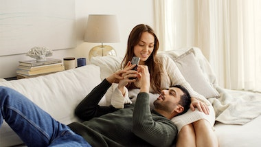 Man lying on the sofa with his head in his partern's lap, they're both looking at a phone