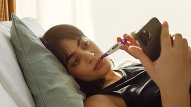 Woman in bed measuring her temperature and looking at a phone