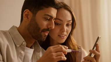 Man and woman holding thermometer and looking at phone together