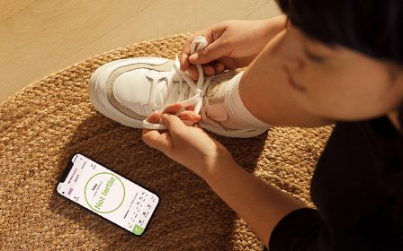 Woman tying her shoe with the Natural Cycles app open on her phone next to her.
