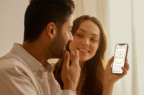 Woman showing her Natural Cycles app to her partner.