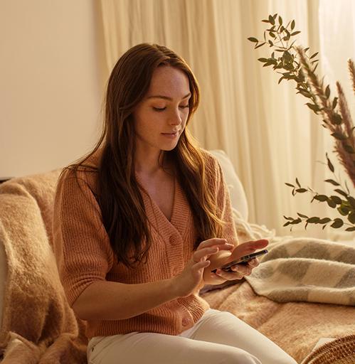 Mulher usando o seu celular enquanto está sentanda em um sofá.