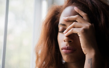Woman with her hand to her forehead looking in pain or stressed