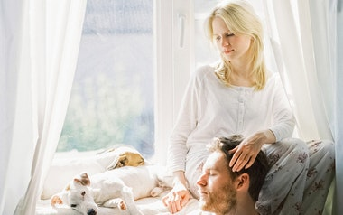 Couple with two dogs sitting in the window