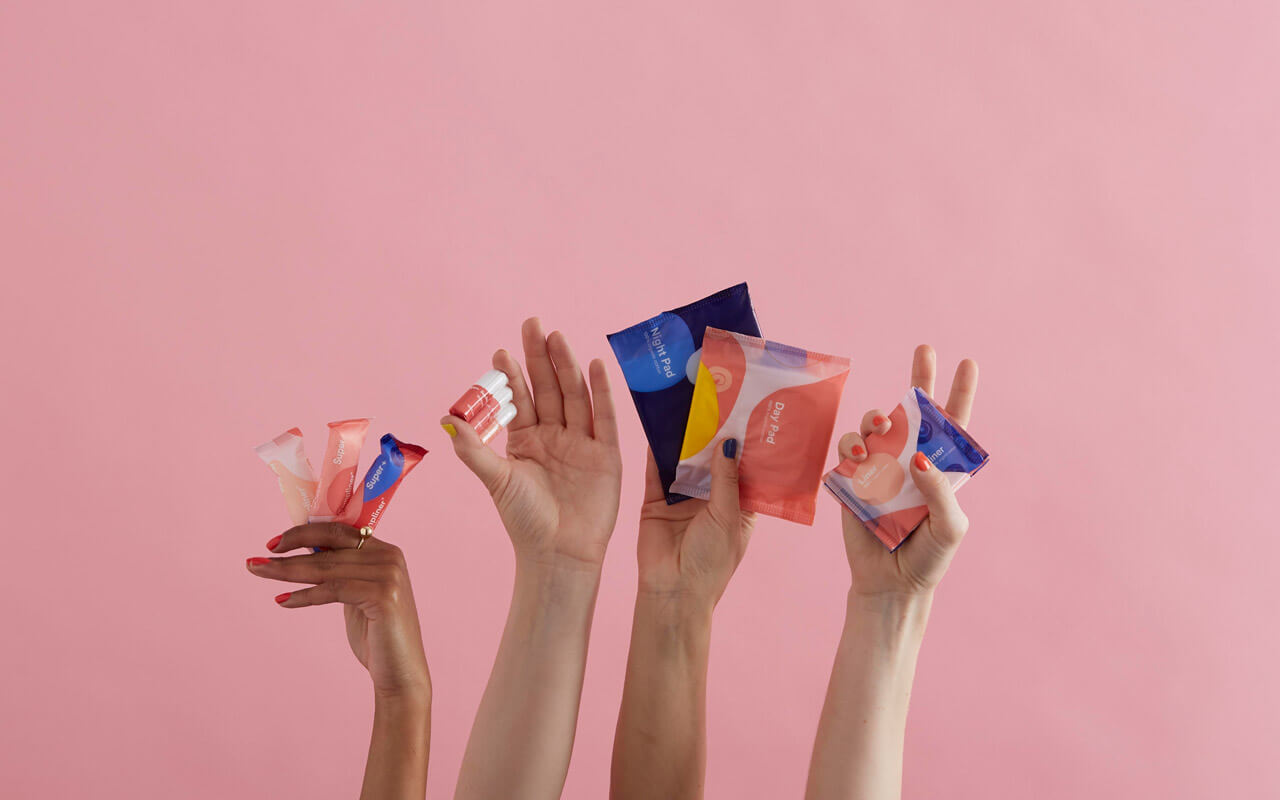 Four hands holding Callaly's period products against an empty pink background. From left to right: tampliners, tampons, pads and liners.