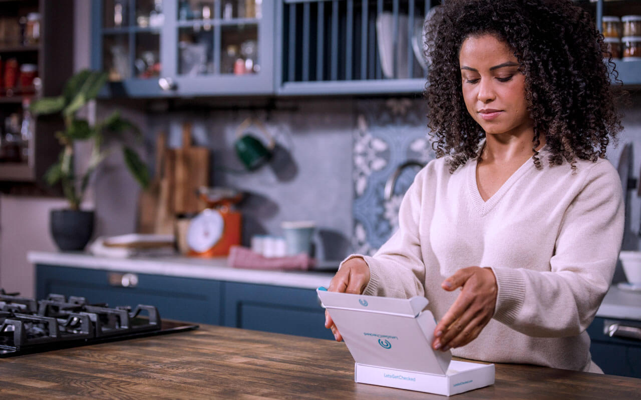 Woman in kitchen opening letsgetchecked test kit
