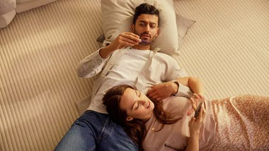 Man and woman lying on the carpet, he's looking at a thermometer, she's looking at her phone.