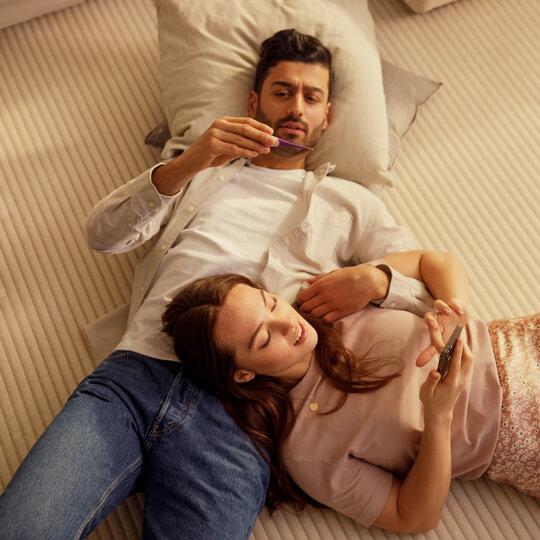 Una pareja recostada con unos almohadones, un termómetro y un smartphone