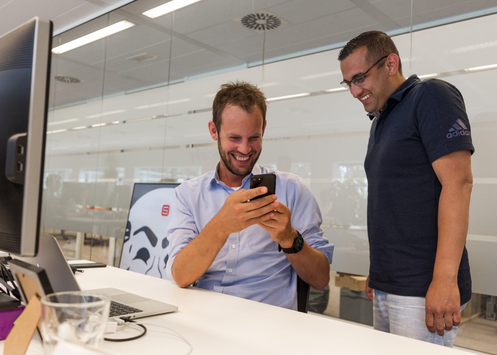 Two men laughing at phone