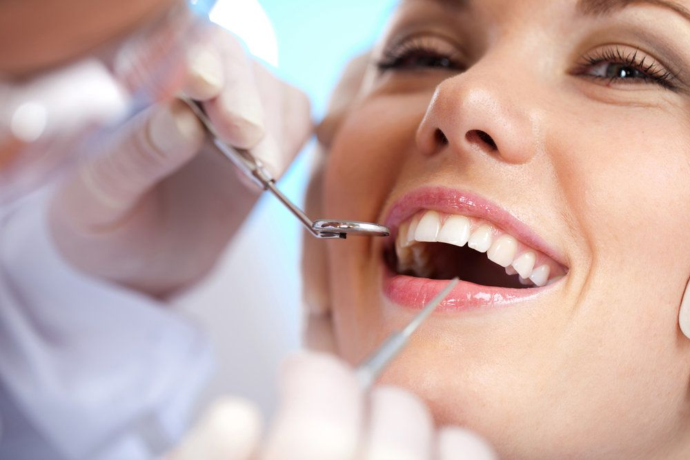 A woman with healthy looking teeth undergoing a dental exam