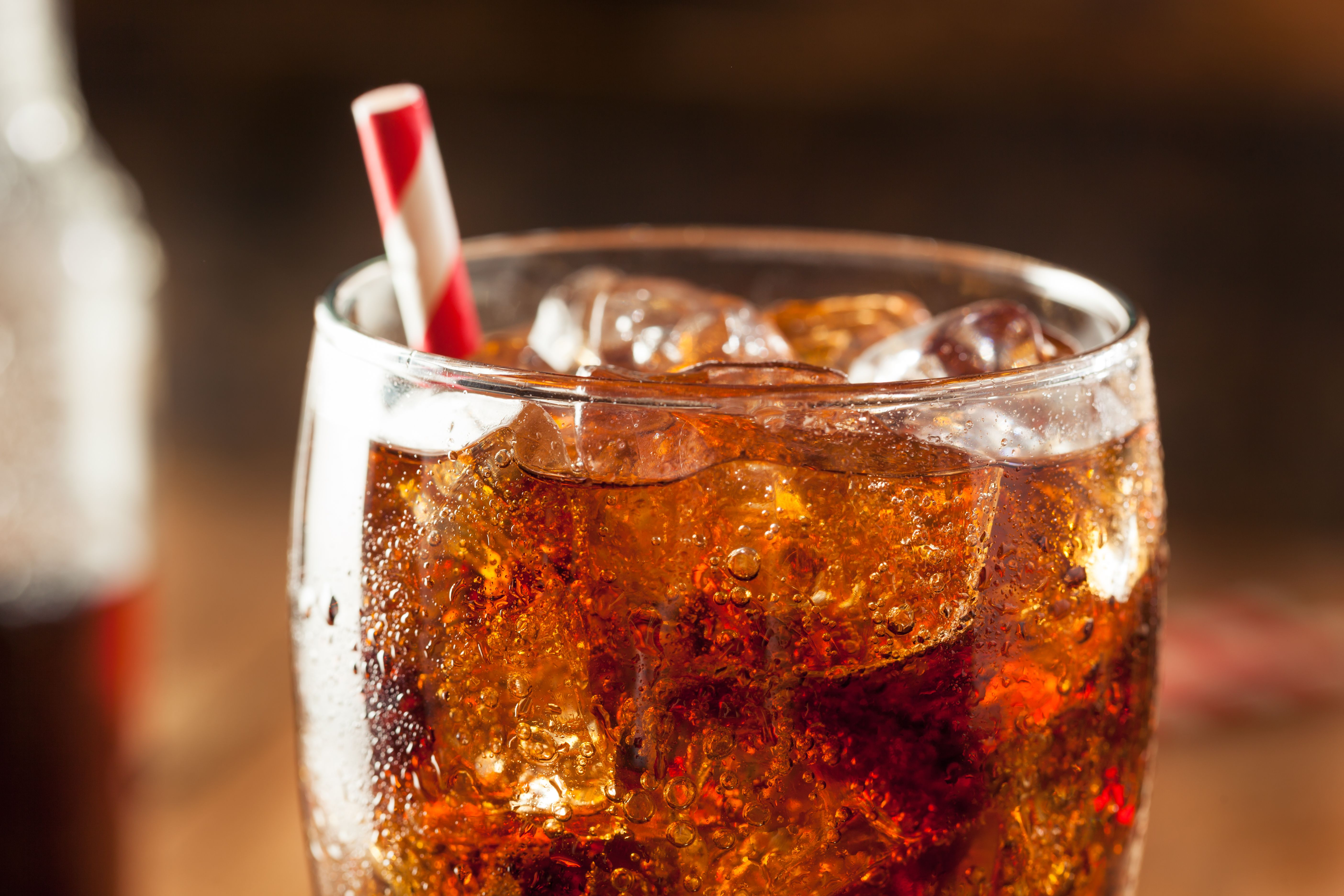 A photograph of a dark soda with a straw in it