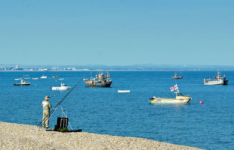 Sea angler at East Beach with the fishing boats in the background