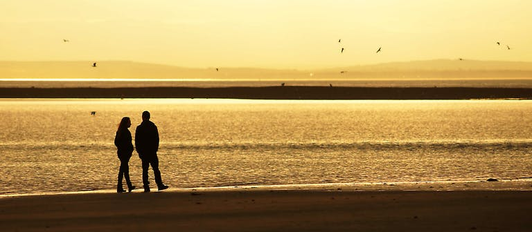 A couple walk along the sand at  Bill Point beach during low tide as the sun sets.  The Isle of Wight can be seen in the background and sea birds flying overhead