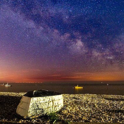 Milkyway captured over East Beach with a overturned boat on the shingle in the foreground