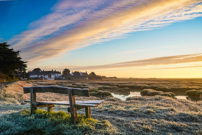 Winter scene of a bench, mudglats and massive skies at Pagham Harbour towards the Crab & Lobster at Sidlesham