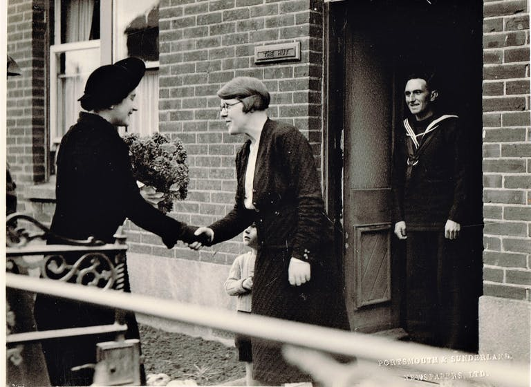 Queen Elizabeth the Queen Mother shaking hands with Bess Maidment as husband Ken dressed in his Naval Uniform stands in the doorway and toddler son is in the background