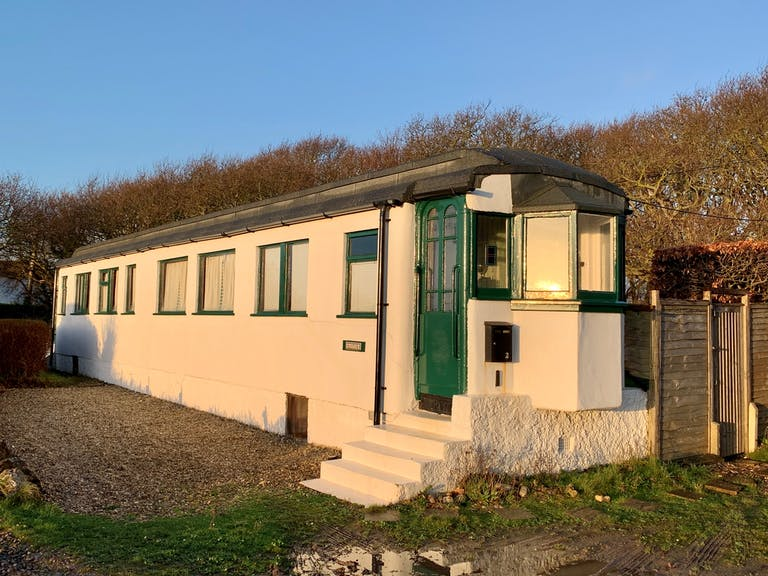 House made out of one railway carriage and rendered in concrete.