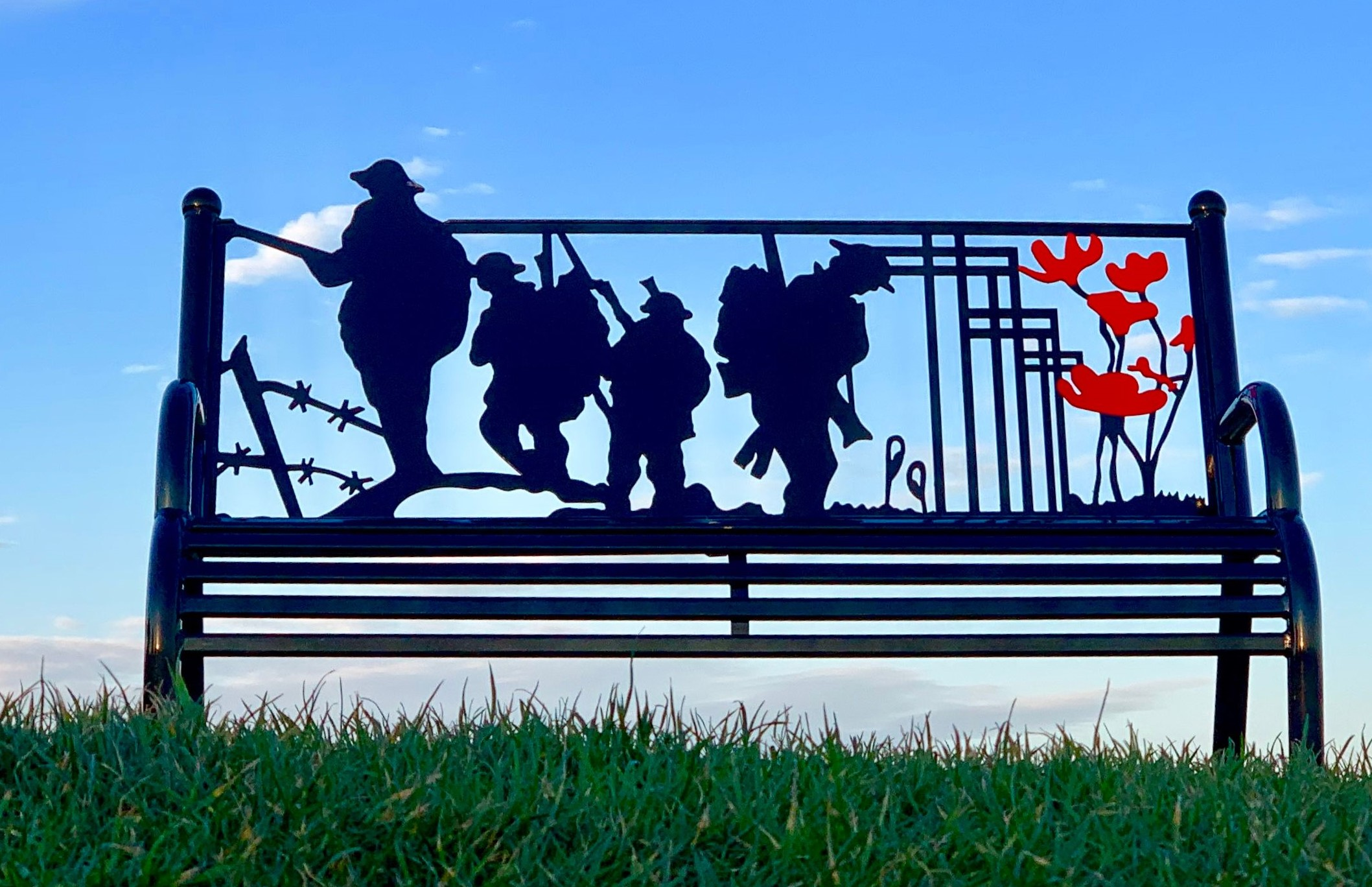 Oval Field Memorial Bench showing four servicemen and 6 poppies