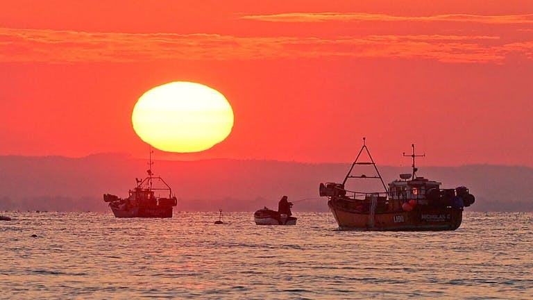 Lone fisherman sandwiched on his dingey with fishing rod, between two larger fishing boats at sunrise