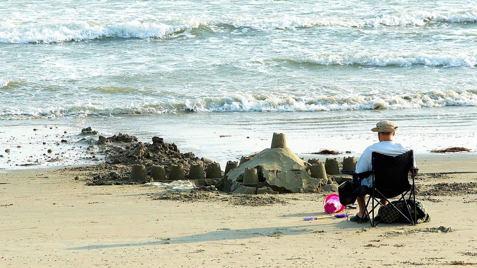 Sandcastles being taken by the incoming tide on Selsey Oval Beach with a man sat in a chair relaxing, facing the sea with a pink sandcastle bucket at his feet.