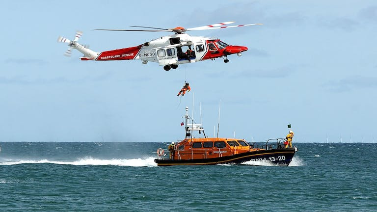 A coastguard helicopter hovers over the RNLI Selsey lifeboat as an individual is hoisted up to the helicopter.  This was part of the display during RNLI Selsey Lifeboat week.
