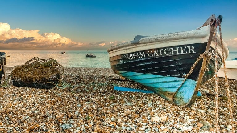A dark blue with light blue bottom boat called Dream Catcher on the shingle at east beach with a lobster pot to its left.  The clouds are creating cotton wool white shapes within the blue sky as the sun captures the sea water