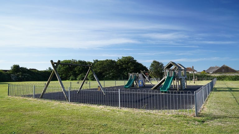 Image of the playground at Hillfield with swings, sides and climbing frame