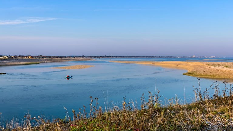 One kayaker in the sea at Pagaham Harbour with grass in the foreground