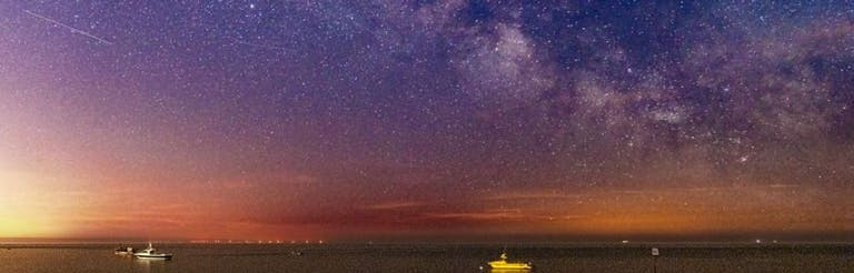 The Milky Way showing in the skies above the sea at East Beach